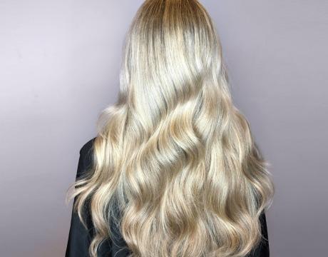 Kvinne med langt, tykt, blondt, bølgete hår