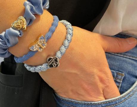 Lekre, blå hårstrikker med charms, på håndledd