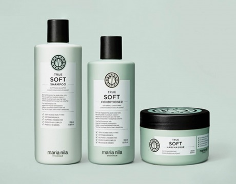 Shampo, balsam og hårmaske i delikat innpakning, oppstilt ved siden av hverandre mot pastellgrønn bakgrunn
